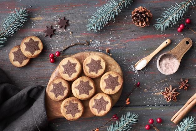 Biscoitos de natal com chocolate estrela sobre uma mesa com cacau, canela e decorado galhos de pinheiro