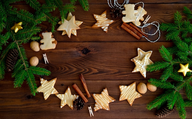 Biscoitos de natal com enfeites na mesa de madeira.