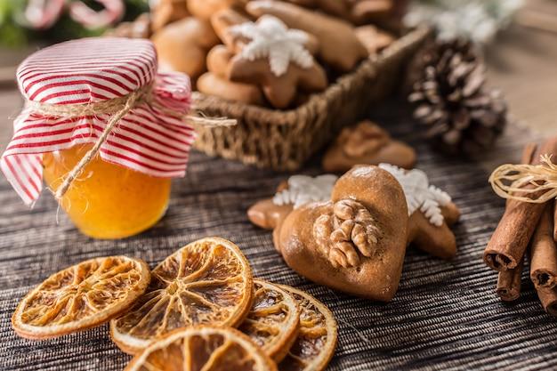 Biscoitos de natal de gengibre com pote de mel na mesa da cozinha - close-up.