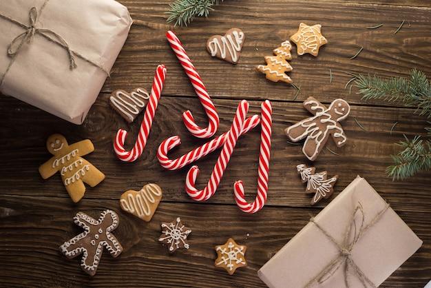 Biscoitos de natal e bastões de doces em fundo de madeira. humor de feriado. pinho. vista do topo.