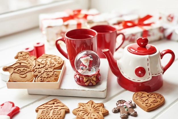 Biscoitos de natal e caneca de chá quente, tempo de natal. pão de natal, doces, café no copo vermelho na mesa de madeira na mesa de janela de dia gelado de inverno. férias acolhedoras em casa. modelo de cartão postal