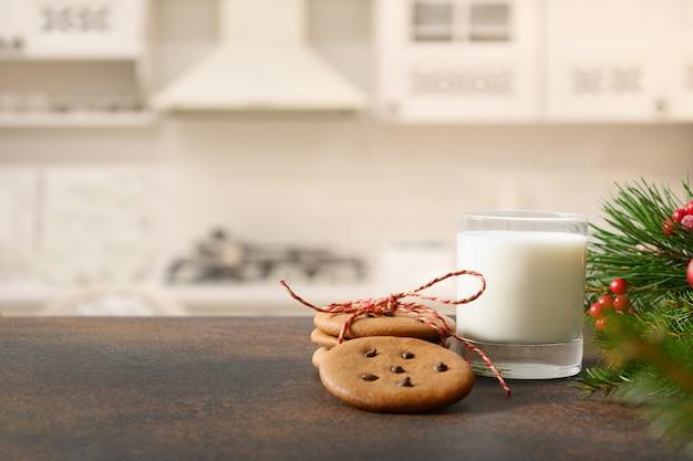 Biscoitos de natal e copo de leite para o papai noel perto da árvore de natal
