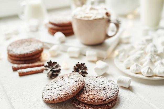 Biscoitos de natal e marshmallows em um branco perto da janela