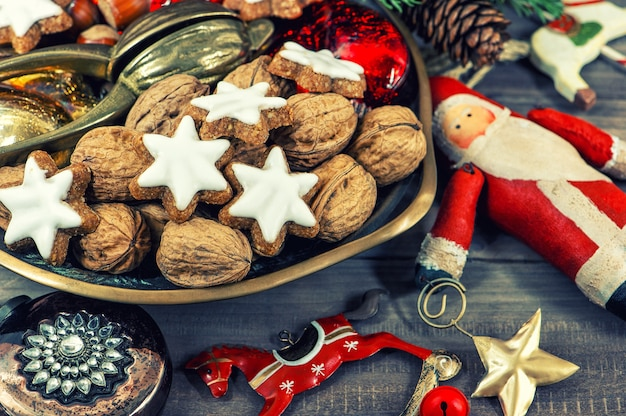 Biscoitos de natal e nozes com decorações vintage em fundo de madeira. imagem em tons de estilo retro