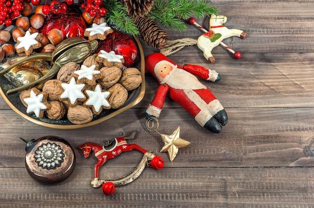 Biscoitos de natal e nozes com enfeites vintage em fundo de madeira