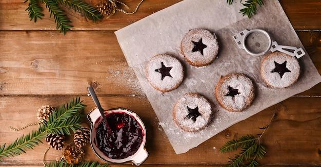 Biscoitos de natal em forma de estrela em uma mesa de madeira. biquitos com geléia e pó, decoração feita de ramos de abeto. vista de cima. copie o espaço