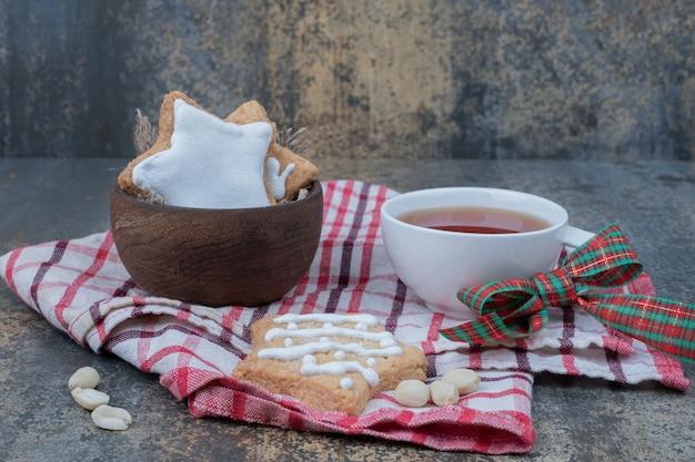 Biscoitos de natal em uma tigela de madeira com uma xícara de chá na toalha de mesa.