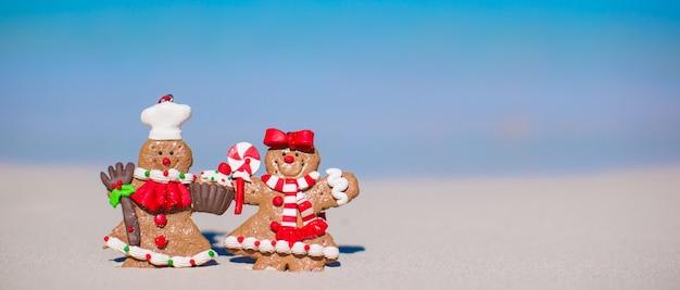 Biscoitos de natal gingerbread man em uma praia de areia branca