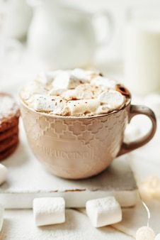 Biscoitos de natal, leite, cacau, marshmallow, merengue em um prato branco perto da janela
