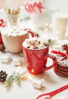 Biscoitos de natal, leite, cacau, marshmallows, doces em um prato branco perto da janela