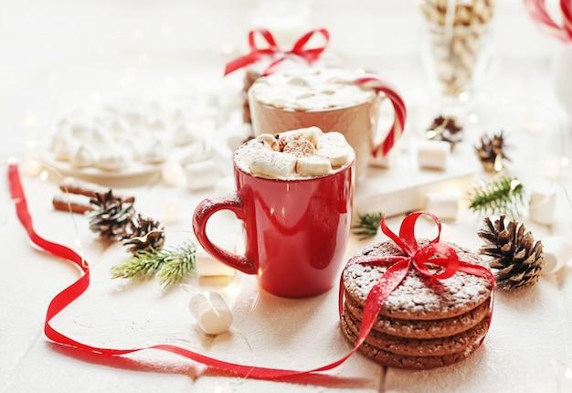 Biscoitos de natal, leite, cacau, marshmallows, prato de doces pela janela