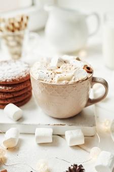 Biscoitos de natal, leite, cacau, marshmallows, prato de merengue pela janela