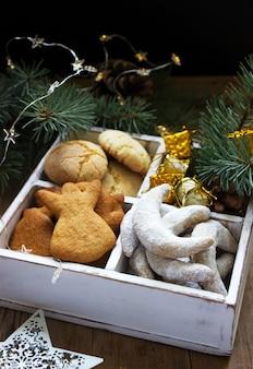 Biscoitos de natal sortidos e decorações de natal em uma caixa de madeira