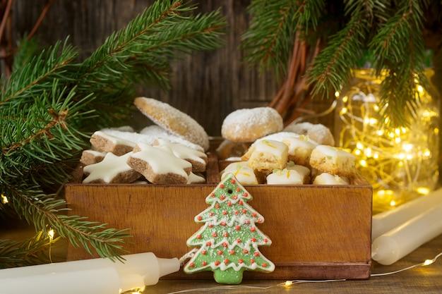 Biscoitos de natal sortidos: estrelas de canela, crescentes de baunilha, cubos de stollen e gengibre em uma caixa de madeira. estilo rústico.