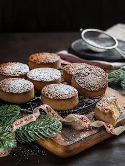 Biscoitos de natal tradicionais com amêndoas e gergelim no fundo escuro de madeira