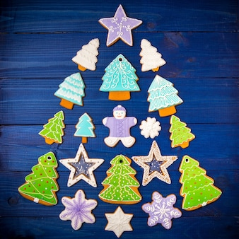 Biscoitos de natal variados em forma de árvore de natal no azul