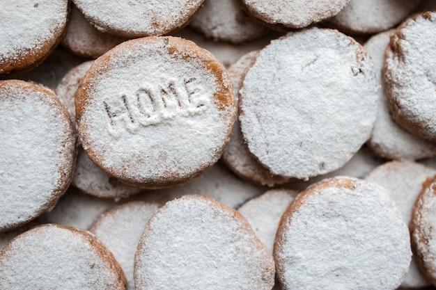 Biscoitos de padaria com decoração de açúcar em pó. inscrição em casa
