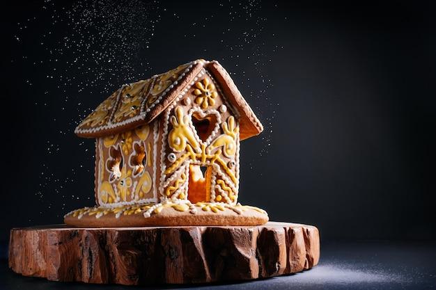 Biscoitos de presente de natal de casa de gengibre no inverno, o conceito de celebração do feriado. neve caindo no fundo preto, borrifando açúcar de confeiteiro na noite de natal