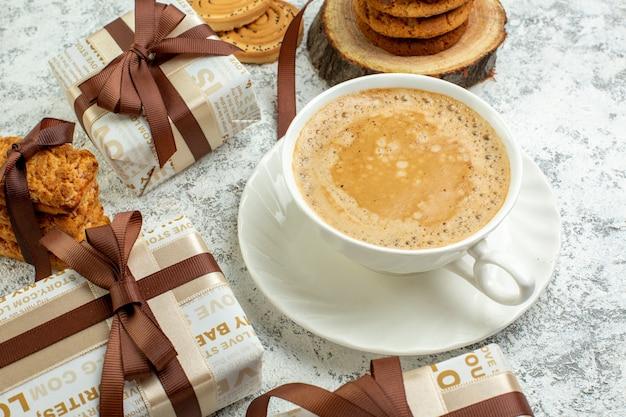 Biscoitos de presentes de dia dos namorados com vista inferior, amarrados com fita na placa de madeira, xícara de café na parede cinza