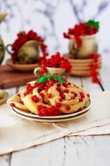 Biscoitos de queijo cottage com groselhas na placa cerâmica com conjunto de chá ou café em cerâmica vintage, hora do chá, café da manhã, doces de verão
