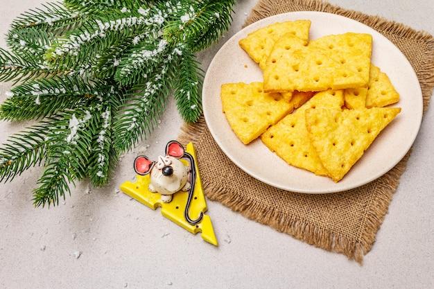 Biscoitos de queijo festivo, conceito de lanche do ano novo. biscoitos, figura de rato, galho de árvore do abeto, neve artificial, guardanapo de pano de saco.