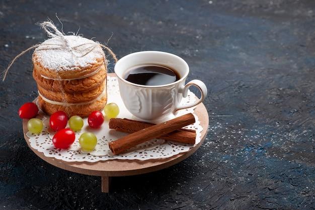 Biscoitos de sanduíche deliciosos amarrados de frente com frutas fatiadas de canela e café no bolo de superfície azul escuro