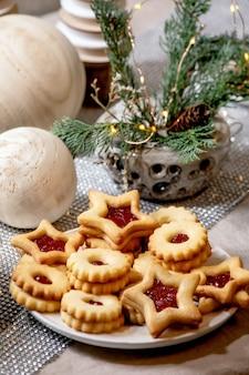 Biscoitos de shortbread caseiros tradicionais do natal linz com geléia vermelha no prato