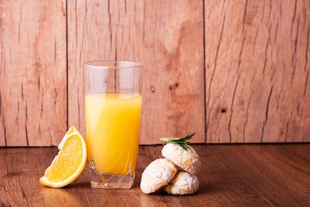 Biscoitos de shortbread laranja com raminhos de gergelim, com laranja fresca e suco em cima da mesa.