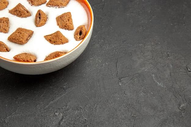 Biscoitos de travesseiro com leite no café da manhã no escuro