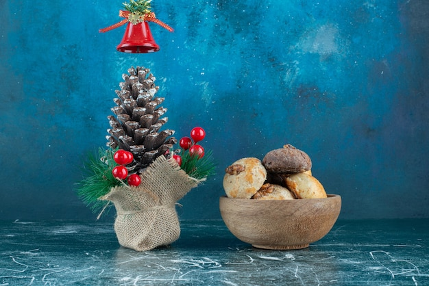 Biscoitos de uma tigela de madeira com pinha de natal.
