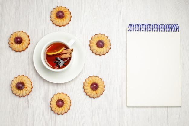 Biscoitos de uva saborosos com uma xícara de chá na mesa branca, torta de biscoito doce de sobremesa vista de cima