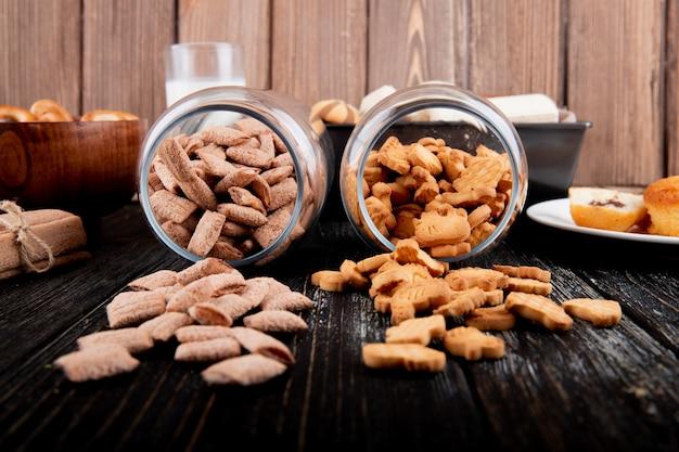 Biscoitos de vista frontal em um pote de flocos de milho e palitos de milho em um fundo preto de madeira