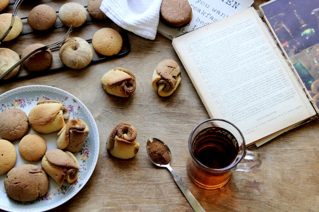 Biscoitos de vista superior com um copo de chá e um livro aberto sobre a mesa