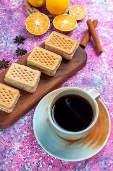 Biscoitos de waffle com recheio de creme de frutas e chá na mesa rosa claro.