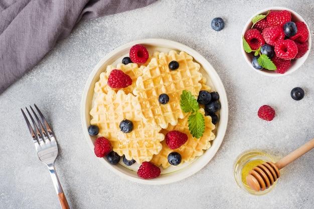 Biscoitos de waffle ondulado com framboesas frescas e mirtilos em um fundo de concreto. copie o espaço.