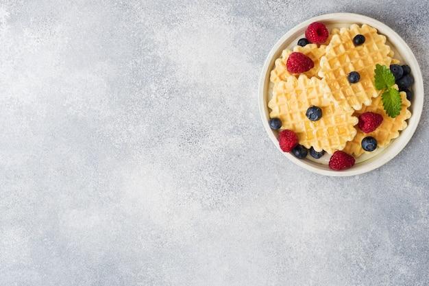 Biscoitos de waffle ondulado com framboesas frescas e mirtilos