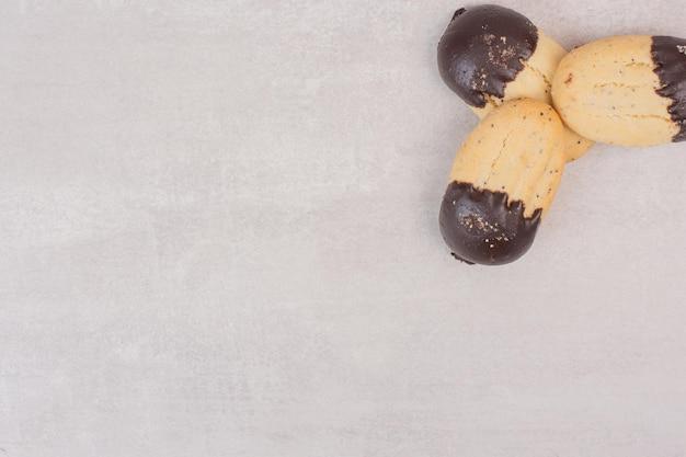 Biscoitos decorados com calda de chocolate na superfície branca.