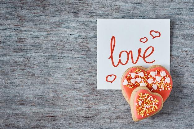 Biscoitos decorados e vitrificados da forma do coração e nota de papel com inscrição amor no fundo cinzento, vista superior. conceito dia dos namorados