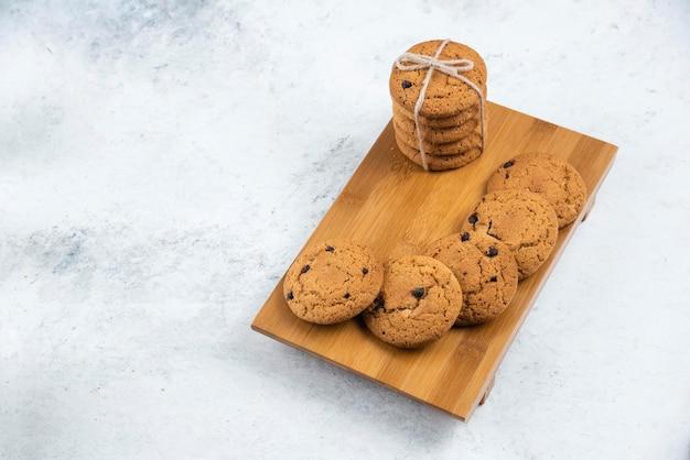 Biscoitos deliciosos com chocolate em uma tábua de madeira.