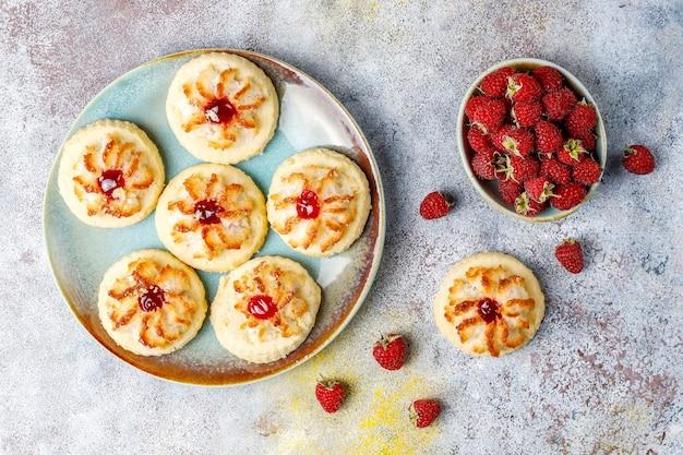 Biscoitos deliciosos com geléia de framboesa e framboesas frescas.