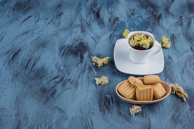 Biscoitos deliciosos com uma xícara de chá de ervas na superfície azul.
