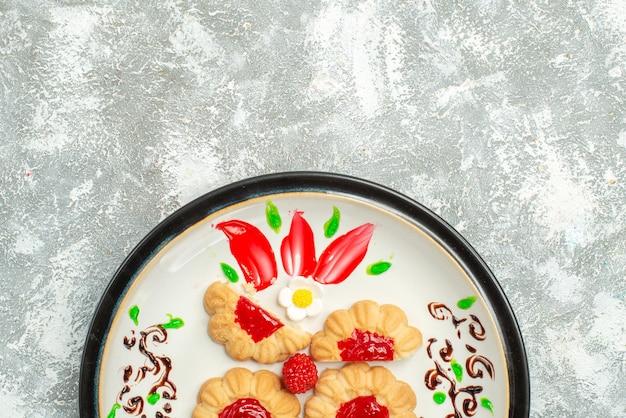 Biscoitos deliciosos de cima com gelatina vermelha dentro do prato no fundo branco biscoito de açúcar bolo biscoito chá doce