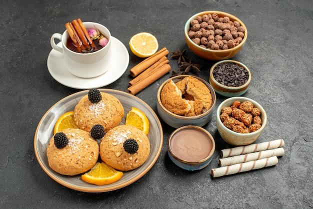 Biscoitos deliciosos de frente com uma xícara de chá em um fundo cinza escuro torta de bolo biscoito de sobremesa