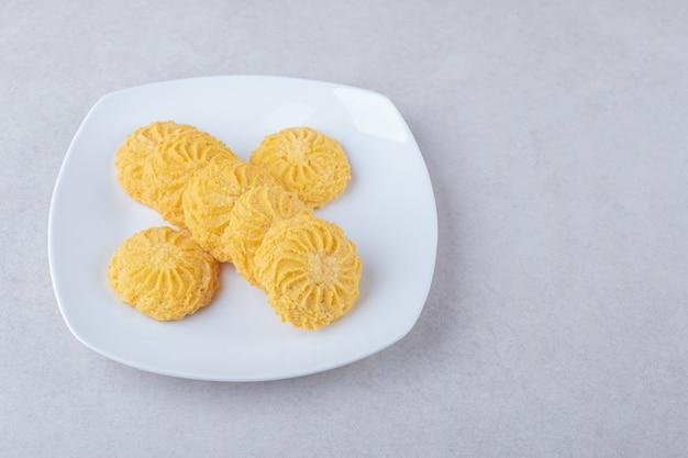 Biscoitos deliciosos em um prato na mesa de mármore.