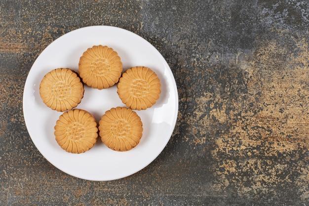 Biscoitos deliciosos recheados com creme no prato branco.