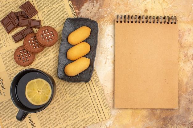 Biscoitos diferentes e chá em uma xícara preta e um caderno na mesa de cores misturadas