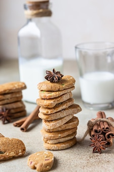 Biscoitos dinamarqueses de manteiga picantes com frutas cristalizadas, canela em pau e erva-doce e copo de leite.