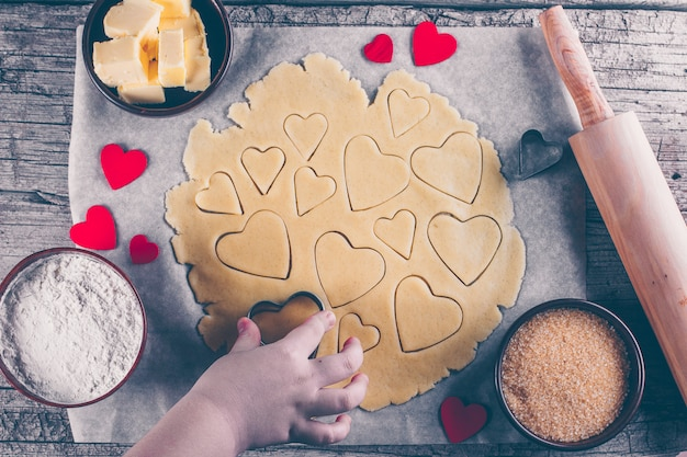 Biscoitos do coração do amor do cozimento para o dia de são valentim. as mãos das crianças para ajudar a preparar biscoitos doces.
