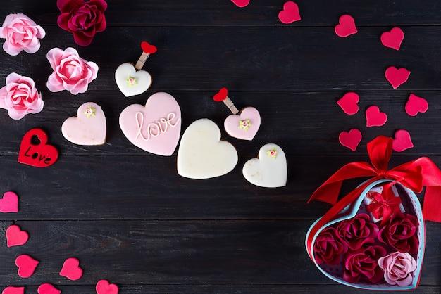 Biscoitos do dia dos namorados em forma de coração no fundo escuro de madeira