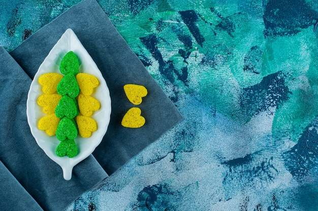Biscoitos doces amarelos e verdes num prato sobre um pedaço de tecido, sobre o fundo azul.